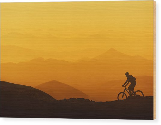 Biker Riding On Mountain Silhouettes Background Wood Print