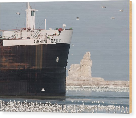 Great Lakes Ship Passing A Frozen Cleveland Lighthouse Wood Print