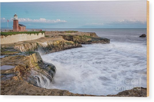 Long Exposure Of Waves Against The Cliff With Lighthouse In Shot Wood Print