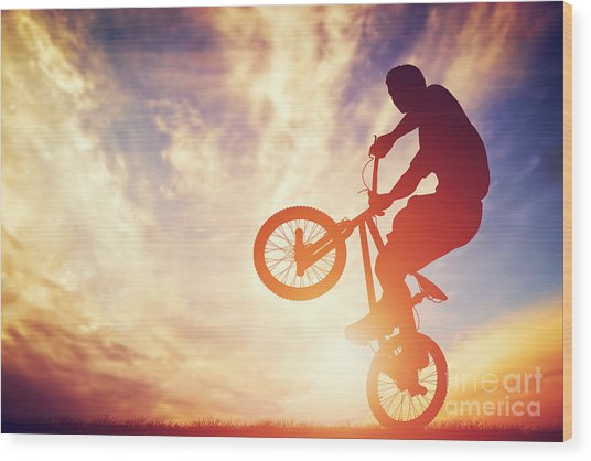 Man Riding A Bmx Bike Performing A Trick Against Sunset Sky Wood Print