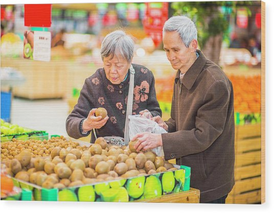 Senior Man And Woman Shopping Fruit Wood Print
