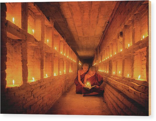 Young Buddhist Monk Are Reading A Book With Light From Candle  Wood Print by Anek Suwannaphoom