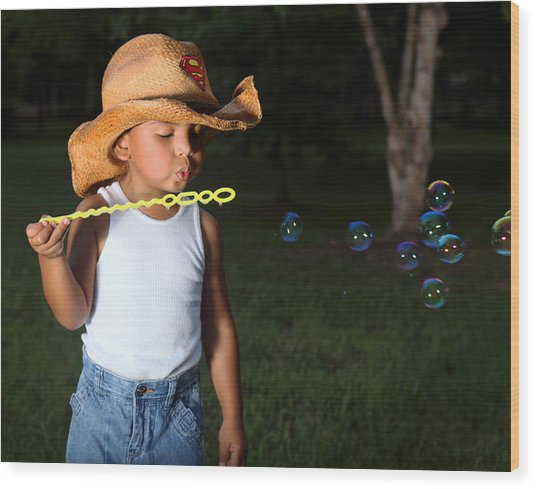 Young Cowboy Blowing Bubbles Wood Print