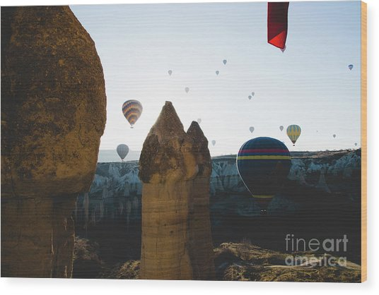hot air balloons for tourists flying over rock formations at sunrise in the valley of Cappadocia. Wood Print