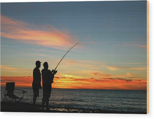 A Silhouette Of Two Men Fishing At Wood Print
