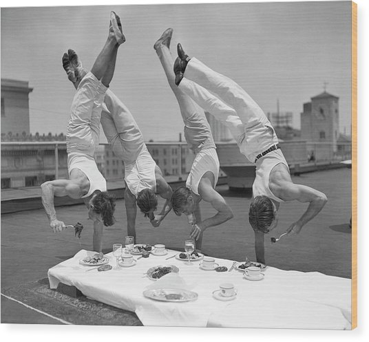 Acrobats Eat While Doing Handstands Wood Print by Bettmann