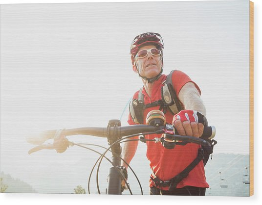 Caucasian Man Pushing Mountain Bike Wood Print by Mike Kemp