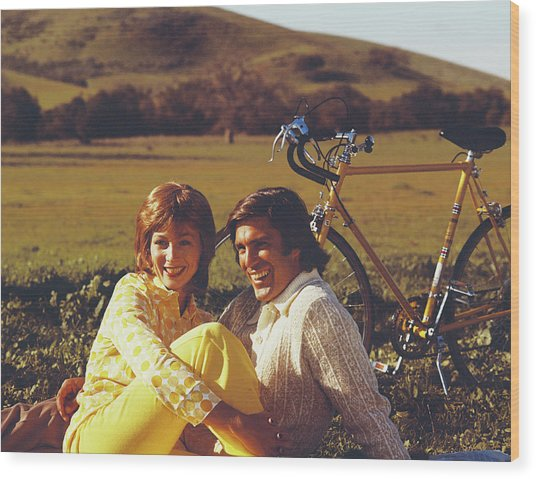 Couple Sitting In Field With Bicycle Wood Print