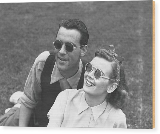 Couple Wearing Sunglasses Sitting On Wood Print by George Marks
