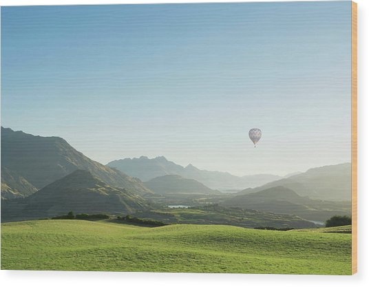 Hot Air Balloon Flying Above Rolling Wood Print by Jacobs Stock Photography Ltd