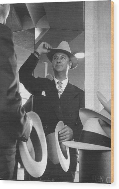 Man Trying On Hats At Nieman Marcus Depa Wood Print by Nina Leen