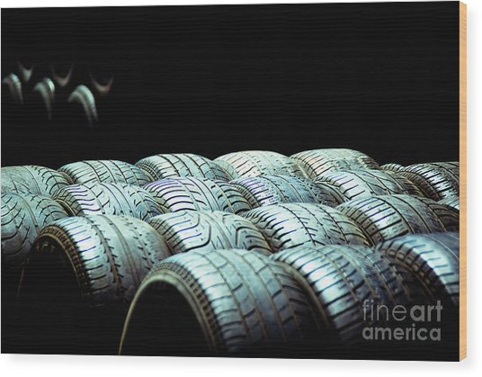 Old Tires And Racing Wheels Stacked In The Sun Wood Print