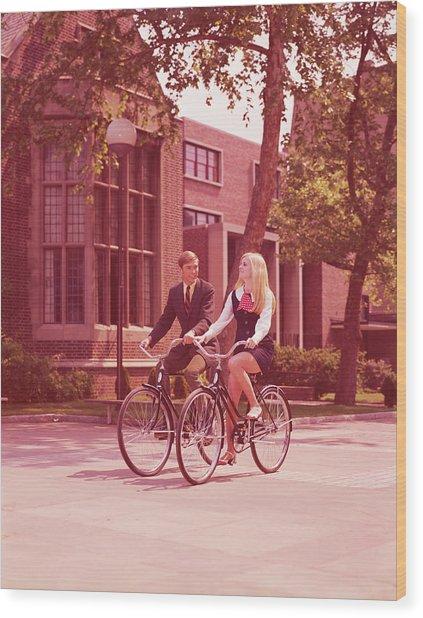 Teenage Couple Riding Bicycles Past Wood Print