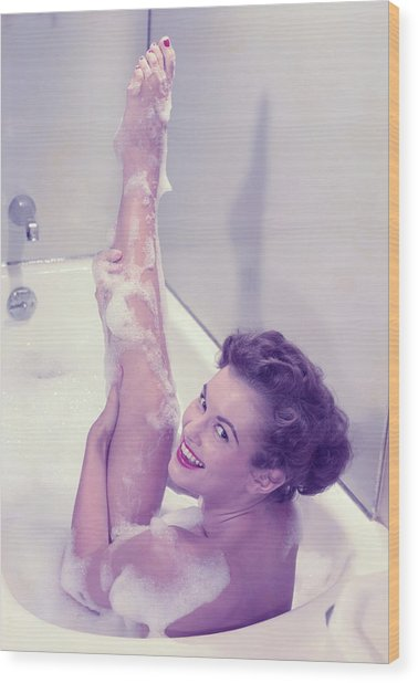 Young Woman In Bath Tub Lathering Wood Print by Hulton Archive