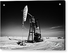 oil pumpjack in winter snow Forget Saskatchewan Canada Acrylic Print by Joe Fox