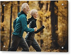 Senior Couple Jogging In A Forest. Acrylic Print by Gilaxia