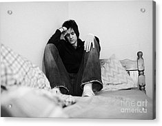 Young Dark Haired Teenage Man Sitting At The Far End Of His Bed In An Untidy Bedsit Bedroom Curled U Acrylic Print by Joe Fox