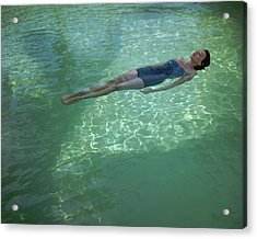 A Model Floating In A Swimming Pool Acrylic Print by John Rawlings