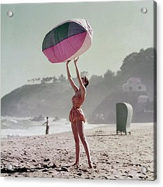A Model Wearing A Bathing Suit Holding Up An Acrylic Print