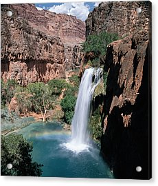 A Waterfall Falls Into Blue-green Water Amongst Green Trees And Jagged Mountain Cliffs Under A Blue Sky With Clouds Acrylic Print by Photodisc