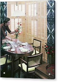 A Woman Arranging Flowers On A Dining Table Acrylic Print