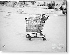 abandoned shopping cart in snow covered supermarket parking lot Saskatoon Saskatchewan Canada Acrylic Print by Joe Fox