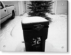 bag sticking out of litter waste bin covered in snow outside house in Saskatoon Saskatchewan Canada Acrylic Print by Joe Fox