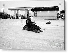 couple on a snowmobile leaving a gas station Kamsack Saskatchewan Canada Acrylic Print by Joe Fox