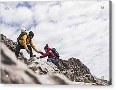 Germany, Bavaria, Oberstdorf, Man Helping Woman Climbing Up Rock Acrylic Print by Westend61