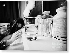 Glass Of Water And Bottles Of Pills On Bedside Table Of Early Twenties Woman In Bed In A Bedroom Acrylic Print by Joe Fox