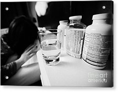 Glass Of Water And Bottles Of Pills On Bedside Table Of Early Twenties Woman Waking In Bed In A Bedr Acrylic Print by Joe Fox