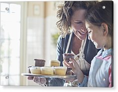 Grandmother Offering Granddaughter Cupcakes Acrylic Print by Caiaimage/Sam Edwards