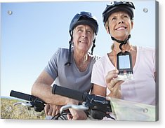 Happy Mature Woman Mountain Biking With Man Using Gps Acrylic Print by OJO Images