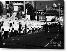 Line Of Psni Land Rovers And Officers On Crumlin Road At Ardoyne Shops Belfast 12th July Acrylic Print by Joe Fox