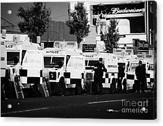 Line Of Psni Landrovers And Officers On Crumlin Road At Ardoyne Shops Belfast 12th July Acrylic Print by Joe Fox