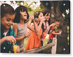 Little Boy Having Fun With Friends In Park Blowing Bubbles Acrylic Print by Wundervisuals