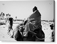 male tourist in desert clothing being led on the back of a camel into the sahara desert at Douz Tunisia Acrylic Print by Joe Fox
