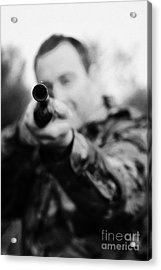 Man In Camouflage Clothes Takes Aim At Camera With Shotgun On December Shooting Day Acrylic Print by Joe Fox