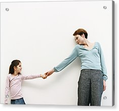 Mother And Her Daughter Stand By A Wall, Reaching Out And Holding Hands Acrylic Print by Dylan Ellis