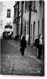 nun with briefcase walking up cobblestone street Kanonicza past tourists in old town krakow Acrylic Print by Joe Fox
