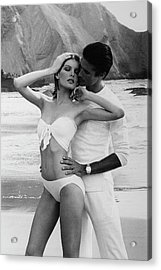 Rene Russo Posing With A Male Model On A Beach Acrylic Print by Francesco Scavullo