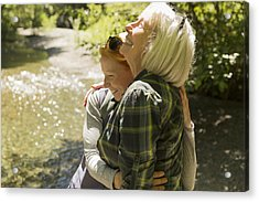 Senior Woman And Daughter Hiking Hugging By River Acrylic Print by Compassionate Eye Foundation/Steven Errico