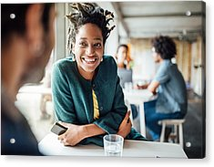 Smiling Businesswoman Sitting With Colleague In Cafeteria Acrylic Print by Luis Alvarez