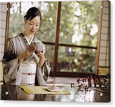 Smiling Woman Drinking Tea During A Japanese Tea Ceremony Acrylic Print by Digital Vision.