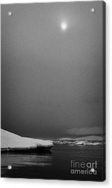 sun breaking through mist and cloud over snow covered ice shelf falling into the sea at Fournier Bay Acrylic Print by Joe Fox