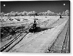 two men on snowmobiles crossing frozen fields in rural Forget Saskatchewan Canada Acrylic Print by Joe Fox