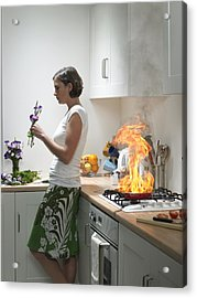 woman Leaning Against Kitchen Worktop Holding Flower, Frying Pan On Fire Behind Acrylic Print by Michael Blann