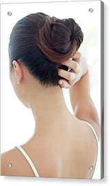 Woman With Hair Bun Scratching Head Acrylic Print by Science Photo Library