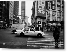 yellow cab taxi blurs past pedestrian waiting at crosswalk on Broadway outside macys new york usa Acrylic Print by Joe Fox