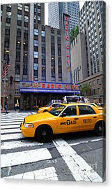 Yellow Cabs Pass In Front Of Radio City Music Hall Acrylic Print by Amy Cicconi